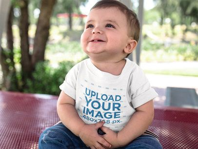 Baby Boy Looking up While Smiling Wearing a Round Neck T-Shirt Mockup a16078