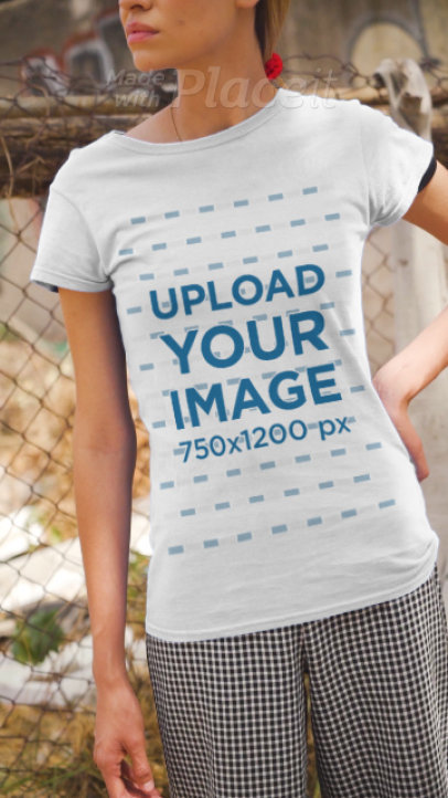T-Shirt Video Maker Featuring a Serious Woman Posing Against a Fence  3388v