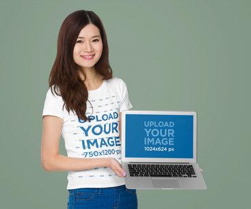 T-Shirt Mockup Featuring a Woman Holding a Macbook Air m7340-r-el2