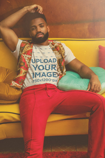 T-Shirt Mockup Featuring a Man with a 70's Outfit Sitting on a Couch m10515
