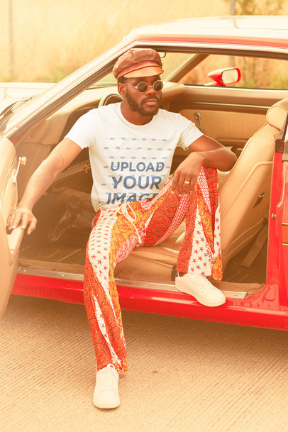 T-Shirt Mockup of a Man Wearing a 70's Outfit on a Muscle Car m10489