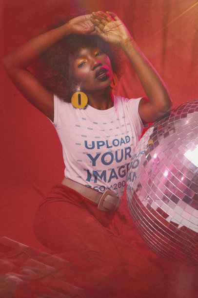T-Shirt Mockup of a Serious Woman in a 70s Outfit Posing by a Disco Ball m10145