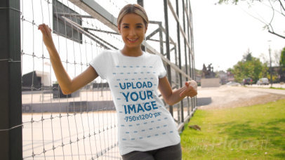 T-Shirt Video Featuring a Smiling Woman Posing by a Fence 3470v