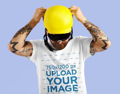 T-Shirt Mockup of a Man with Tattoos Putting on a Sports Helmet M6347-r-el2