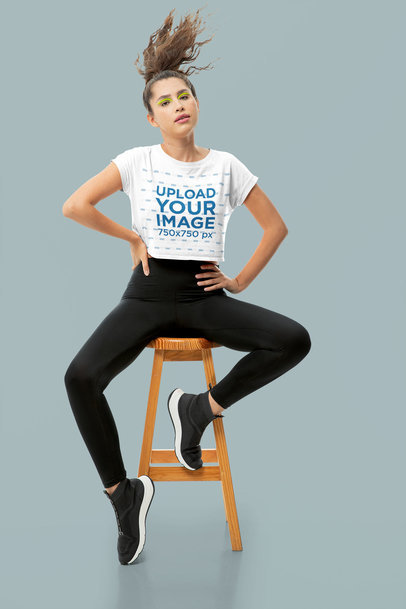 Crop Top Mockup Featuring a Woman With an Athleisure Look Sitting on a Stool m10768