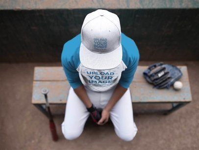 Top Shot of a Seated Baseball Player Wearing a Hat Mockup and a Raglan T-Shirt a16174