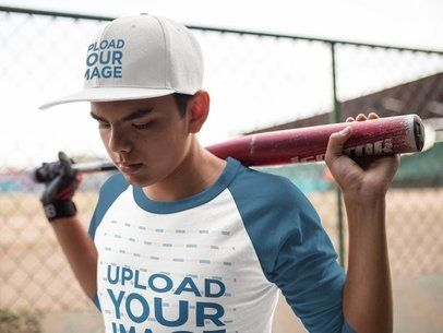 Boy Holding a Bat on His Shoulders Wearing a Baseball Hat Mockup and a Raglan Tee a16171