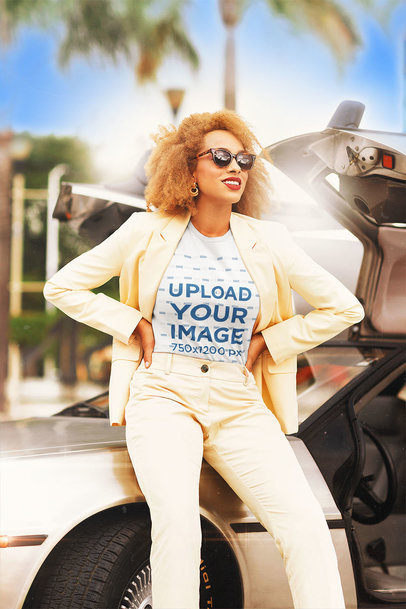 T-Shirt Mockup Featuring a Curly-Haired Woman Sitting on a Retro Car's Bonnet m12033