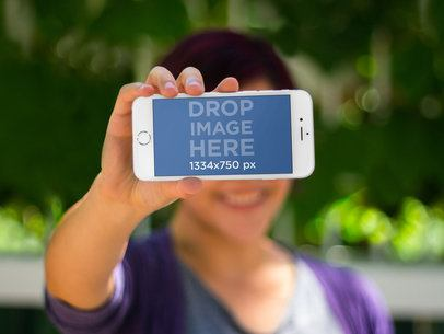Mockup of a Woman Showing off Her iPhone 6 Screen Bokeh