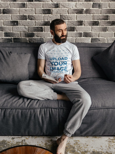 V-Neck T-Shirt Mockup of a Bearded Man Reading on a Comfy Couch m12487-r-el2