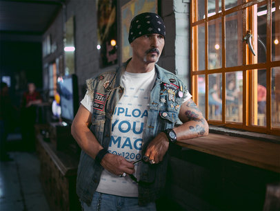 Transparent Mockup of a Biker Wearing a Round Neck Tshirt and a Denim Vest Looking Through a Window 20253