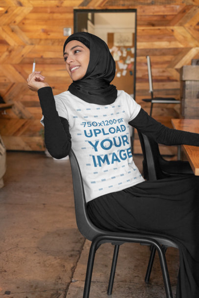 Transparent T-Shirt Mockup Featuring a Woman at a Coffee Store Holding a Pen 32396
