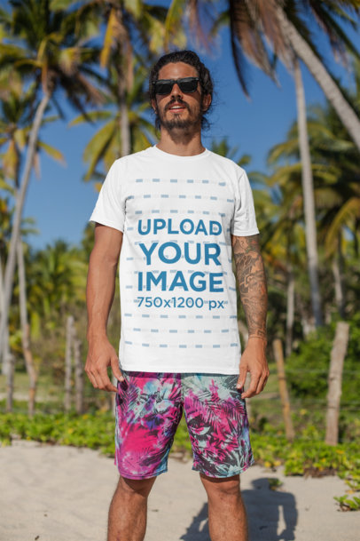 Transparent T-Shirt Mockup of a Man with Surfer Shorts Standing at the Beach 26755