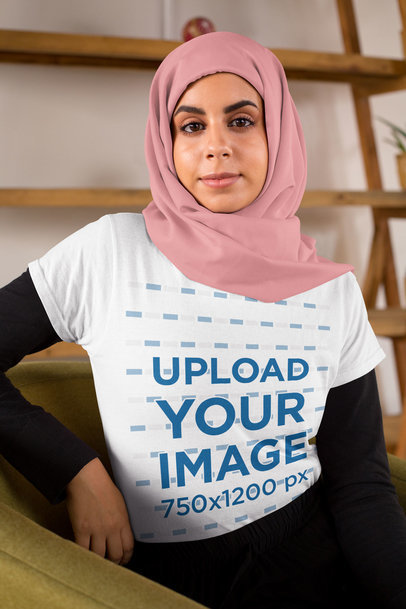 Transparent T-Shirt Mockup Featuring a Woman with a Hijab Sitting on a Sofa 28272