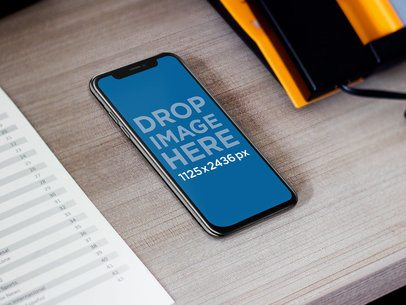 Space Gray iPhone X Mockup at a Hotel Desk a17564