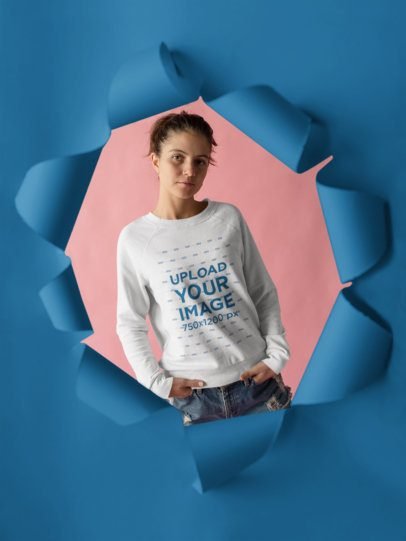 Mockup of a Crewneck Sweater Being Worn by a Pretty Woman Behind a Hole in a Paper a18501