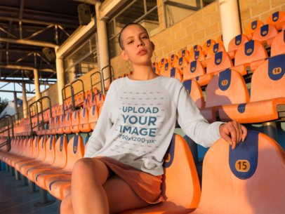 Girl Wearing a Crewneck Sweater Template While Sitting at a Stadium on a Sunny Day a18406