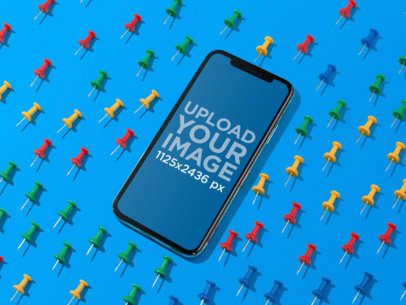 Mockup of a Black iPhone X on a Blue Surface Surrounded by Board Pins 19116a