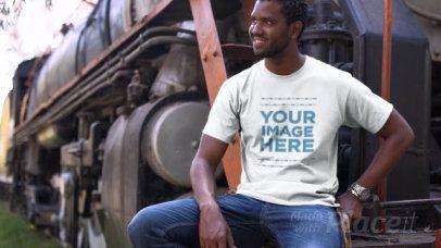 Smiling Black Man Sitting Next to a Train Wearing a T-Shirt Video Mockup a12779