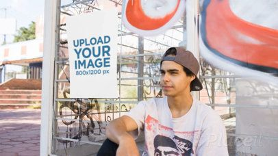 Poster Video Mockup Glued to a Bus Stop With Graffities While Near a Young Skater Guy Sitting a13899