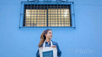 Girl Holding a Tote Bag Video While Standing Near a Blue Bricks Wall a13716