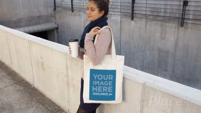 Young Girl Holding a Tote Bag While Waiting And Drinking A Coffee Video Mockup a13770b