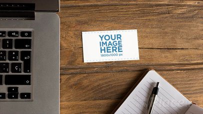Business Card Moving in Stop Motion on a Wooden Desk Near a Laptop and a Note Pad a13869
