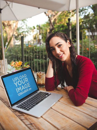 Happy Woman Sitting on a Bench Showing You a MacBook Pro Mockup a19513
