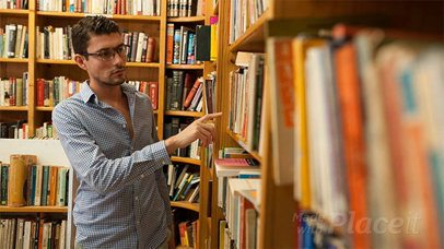 Young Dude Picks Up a Book From a Bookshelf at the Library and Looks At It in Stop Motion a13852