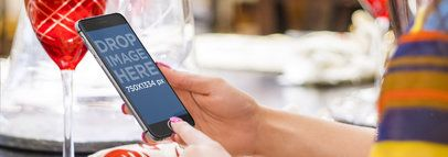 Mockup of a Woman Using an iPhone 6 in Portrait Position at Dinner Wide