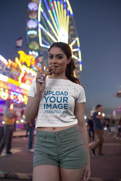 Girl Wearing a T-Shirt Mockup Having an Ice at an Amusement Park a19444