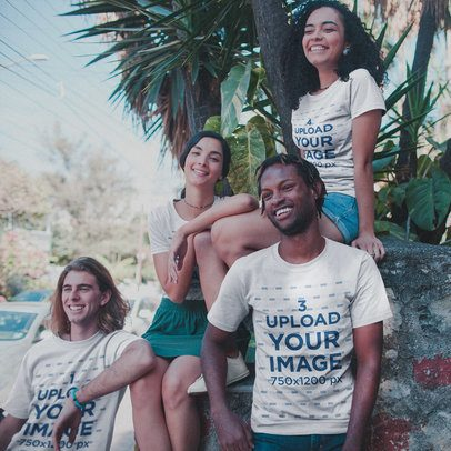 Interracial Group of Four Friends Living the Van Life Wearing T-Shirts Mockup Under Plants a20110