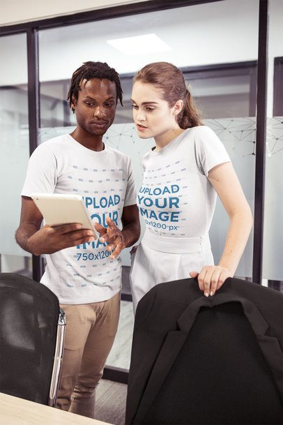 Interracial Group of a Man and a Woman Wearing T-Shirts Mockup While Talking About Work a20518