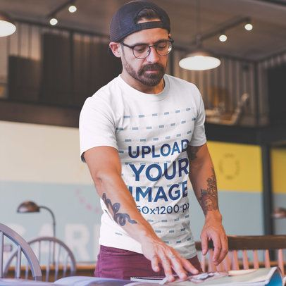 Man with Tattoos Wearing a Tshirt Mockup at a Startup a20399