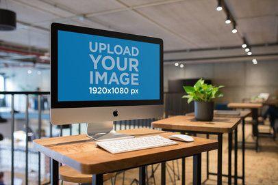 Angled Shot of an iMac Mockup at a Workstation Wooden Desk a21162