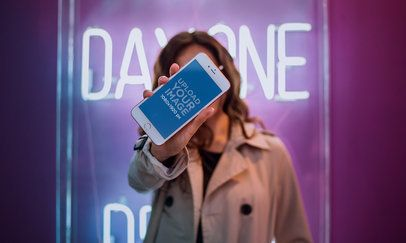 Mockup of a Woman Holding an iPhone 7 Plus Against her Face while Near a Neon Sign a21279