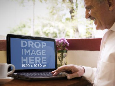 Elderly Man Using HP Laptop While Drinking Coffee In a Terrace