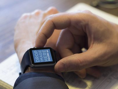 Stock Photo of Man Using Black Apple Watch While Working
