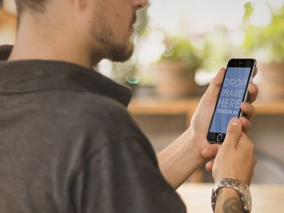 Mockup of Young Tattooed Man Using his iPhone 6 at an Outdoor Restaurant