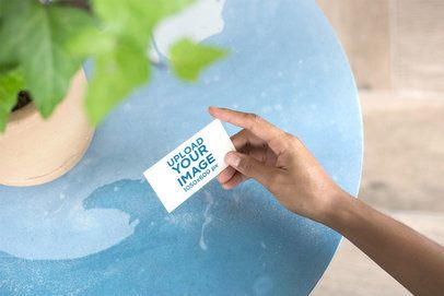 Mockup of a Business Card Being Held Next to a Plant Pot 21905