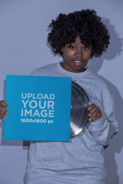 Mockup of a Girl Wearing a Gray Sweatshirt Holding a Vinyl Album Cover 22115