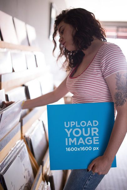 Mockup of a Young Woman Holding a Vinyl Record Cover at a Record Store 22094