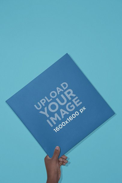 Vinyl Album Cover Mockup Held Over a Solid Background 22118