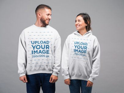 Mockup of a Man Wearing a Sweater and a Girl Wearing a Hoodie Smiling at Each Other in a Studio Setting 22350