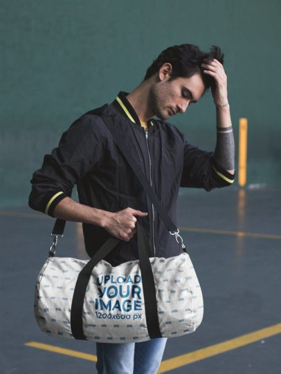 Mockup of a Duffle Bag Held by a Man in a Sports Facility 23240