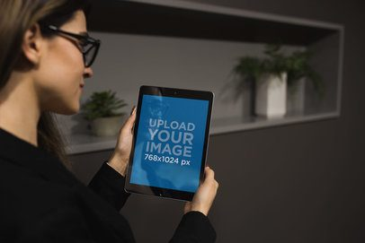 iPad Mockup of a Woman with Glasses Standing by Plant Pots 22810