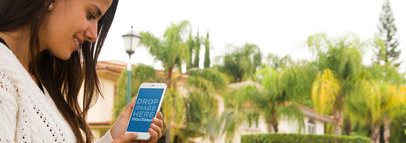 Mockup of a Young Woman Using an iPhone 6 Outside her House a4426