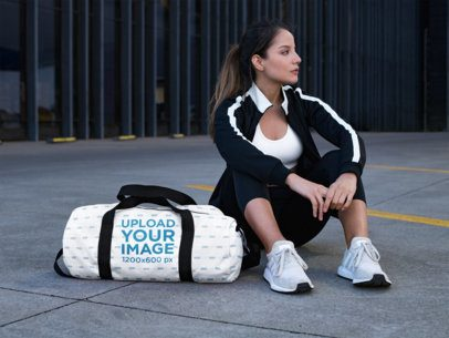 Mockup of a Woman Sitting Next to a Duffle Bag 23050
