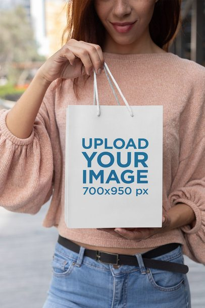 Mockup of a Young Woman Holding Up Her Small Gift Bag 24046