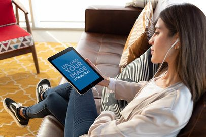 Ipad 6 Mockup of a Girl with White Earphones Listening to a Podcast 24790